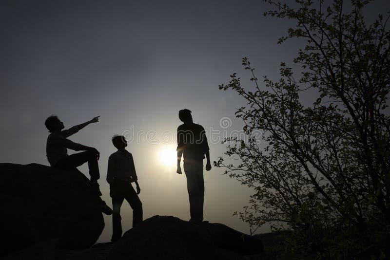 Silhouetten van mensen op rotsen stock foto