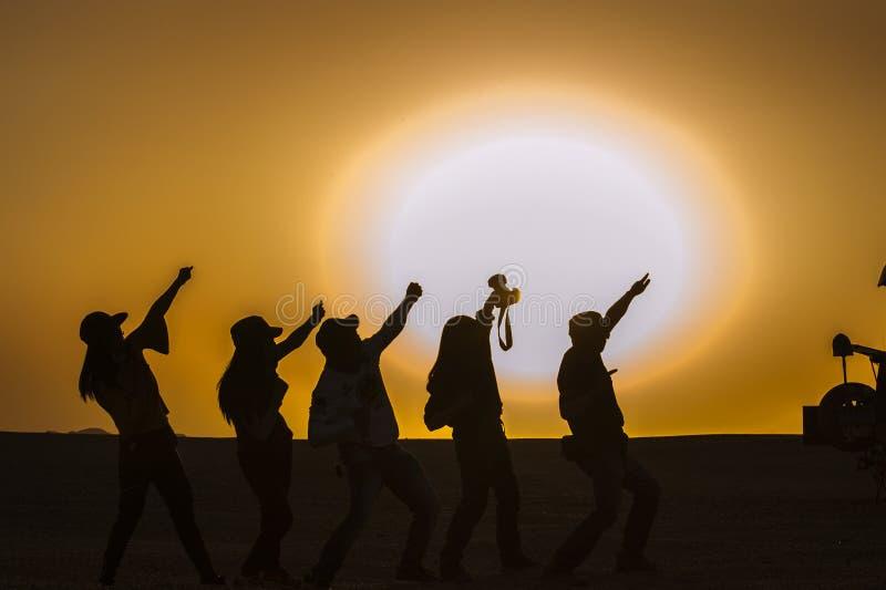 Silhouetten van mensen in woestijn stock fotografie
