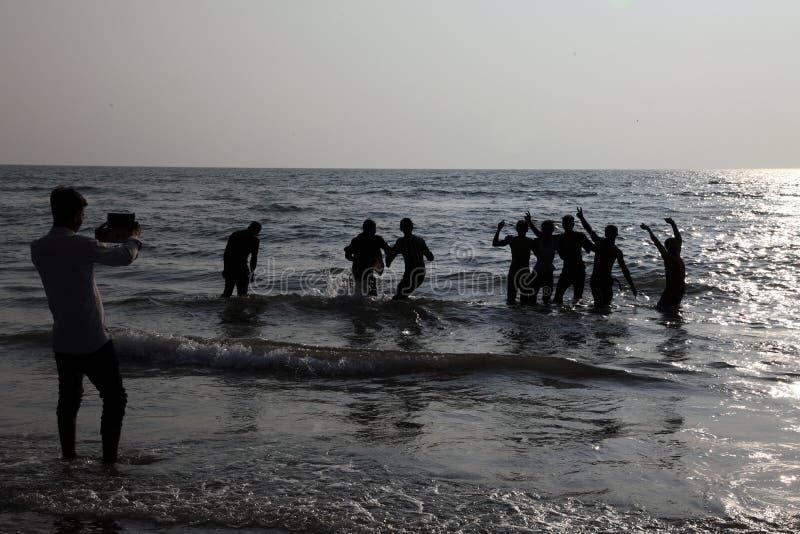 Silhouetten van mensenspel in de golven in het Bekal-strand royalty-vrije stock foto