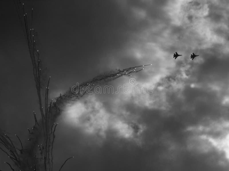 Silhouetten van militaire vliegtuigen tegen stock afbeelding