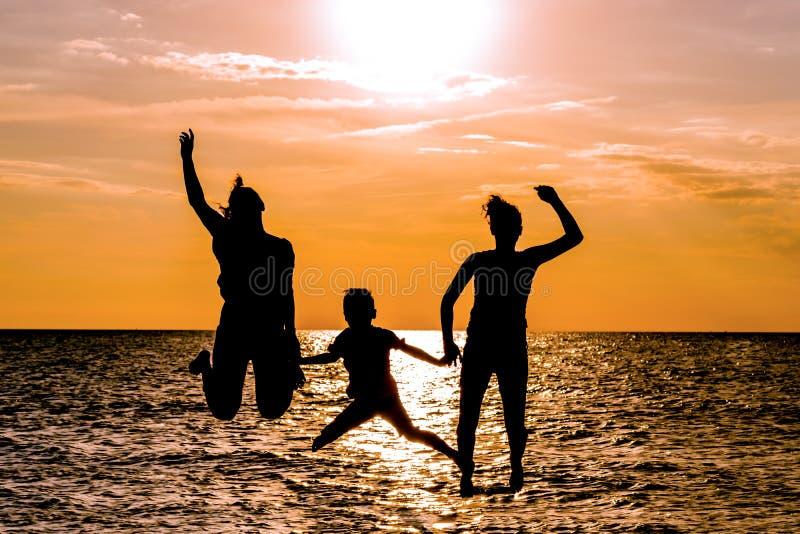 Silhouetten van moeder en jonge geitjes die op strand bij zonsondergang springen stock fotografie
