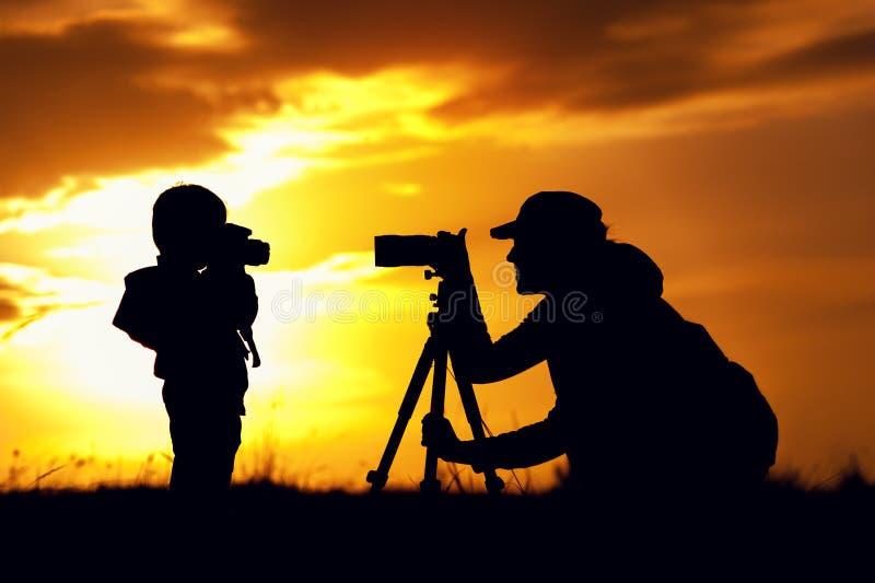 Silhouetten van moeder en kind die beelden nemen stock foto
