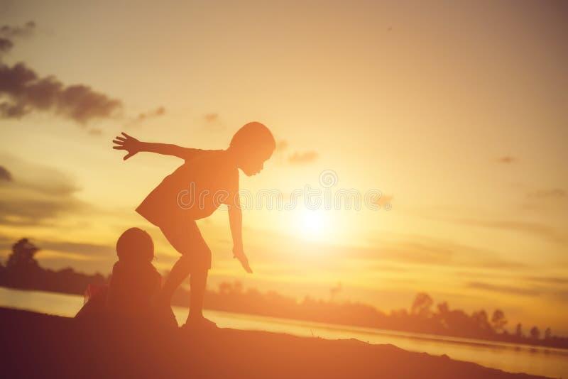 Silhouetten van moeder en weinig dochter die bij zonsondergang lopen stock foto