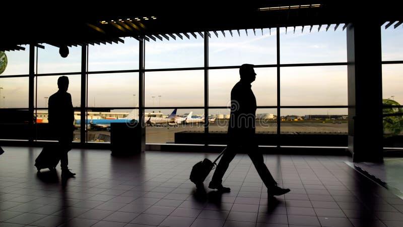 Silhouetten van passagiers die bij eindzaal lopen, zakenreis, luchthaven royalty-vrije stock afbeelding