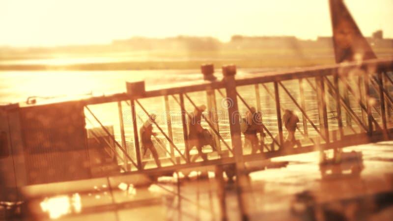 Silhouetten van passagiers die in een glas straalbrug lopen Het verlaten van een vliegtuig bij de luchthaven in de avond royalty-vrije stock foto