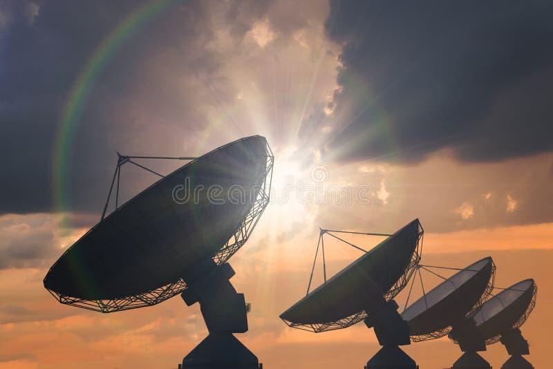 Silhouetten van serie van satellietschotels of radioantennes bij zonsondergang royalty-vrije stock foto's