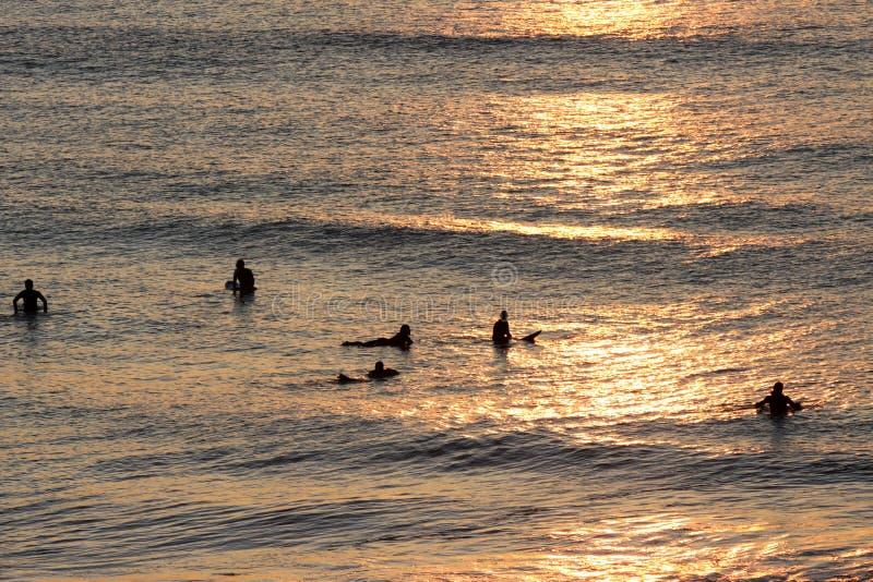 Silhouetten van surfers die op een golf dichtbij het strand bij zonsondergang wachten stock afbeeldingen