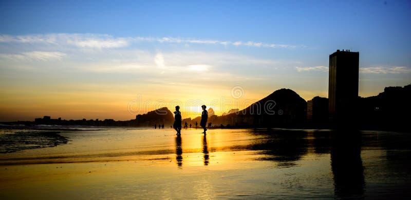Silhouetten van twee lopende jongens op de achtergrond van de mooie zonsondergang bij Copacabana-strand, Rio de Janeiro, Brazilië royalty-vrije stock foto's