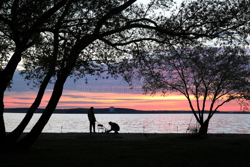 Silhouetten van twee vissers onder grote bomen stock fotografie