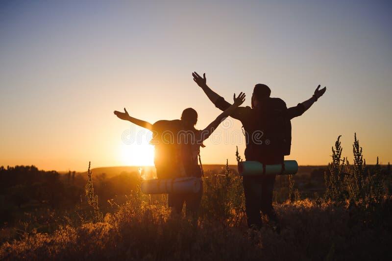 Silhouetten van twee wandelaars die met rugzakken bij zonsondergang lopen Trekking en het genieten van de van zonsondergangmening stock foto