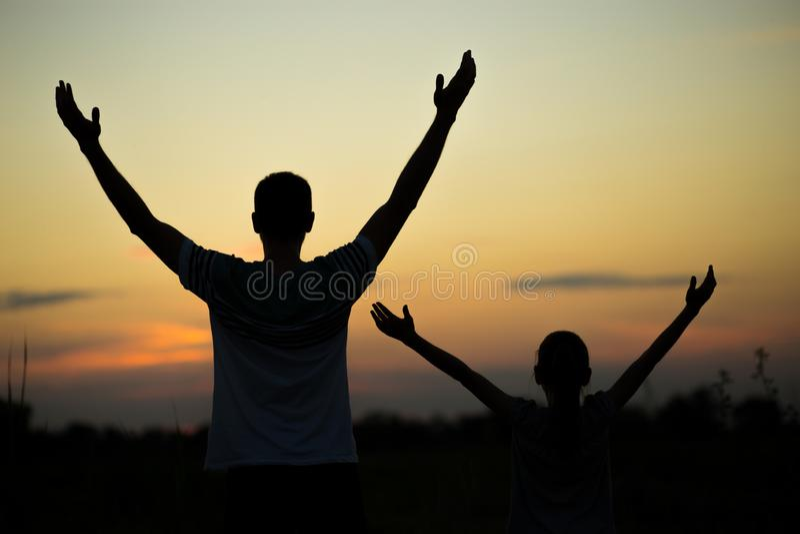 Silhouetten van vader en dochter met handen die omhoog pret hebben, tegen zonsonderganghemel stock foto's
