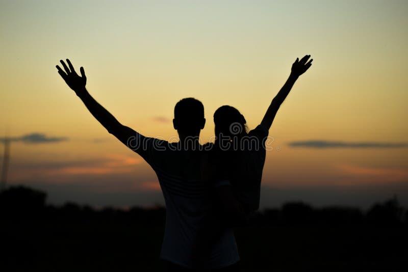 Silhouetten van vader en dochter op zijn schouders met handen die omhoog pret hebben, tegen zonsonderganghemel royalty-vrije stock afbeelding