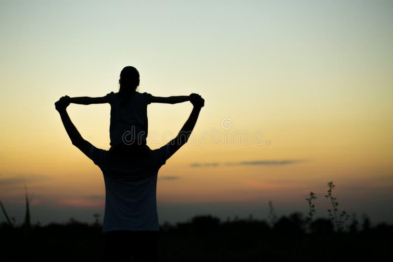 Silhouetten van vader en dochter op zijn schouders met handen die omhoog pret hebben, tegen zonsonderganghemel ouderschap stock foto's