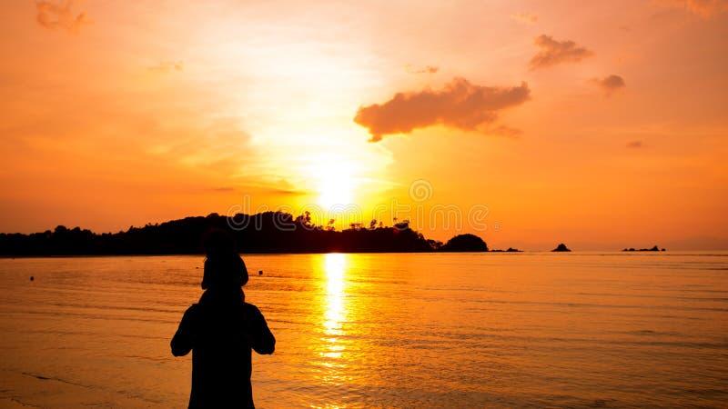 Silhouetten van vader en zoon en zonsondergangmening over het overzees royalty-vrije stock fotografie
