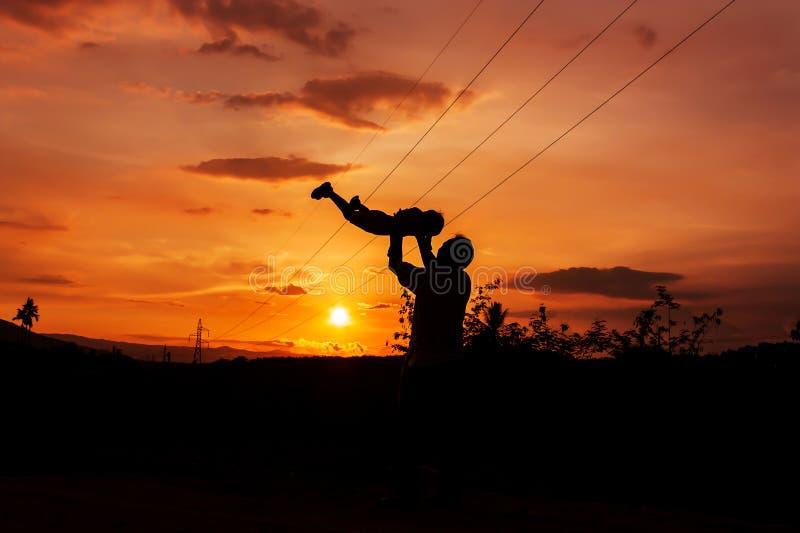 Silhouetten van vader en zoonszonsondergangachtergrond stock fotografie