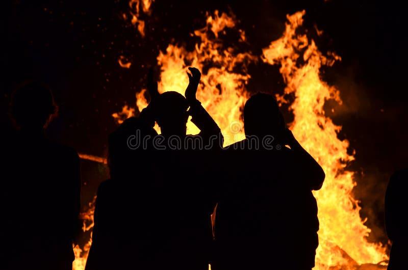 Silhouettenjongeren rond de brandvuur van gebrulvlammen royalty-vrije stock afbeelding