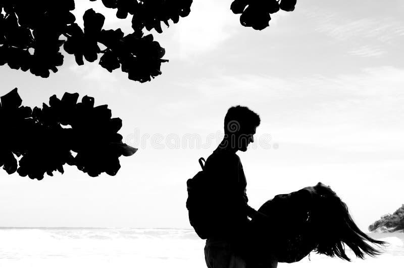 Silhouettenpaar die van het strand genieten Zwart-wit beeld stock afbeeldingen