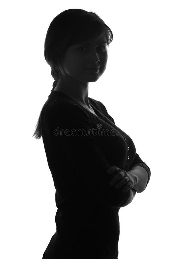 Silhouetteof een wijfje met haar wapens vouwt haar borst op stock foto's