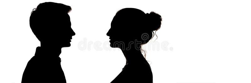 Silhouetteof en grabb och en flicka som ser de, huvudprofil av förälskade tonåringar, begreppet av förhållanden och känslor royaltyfri foto