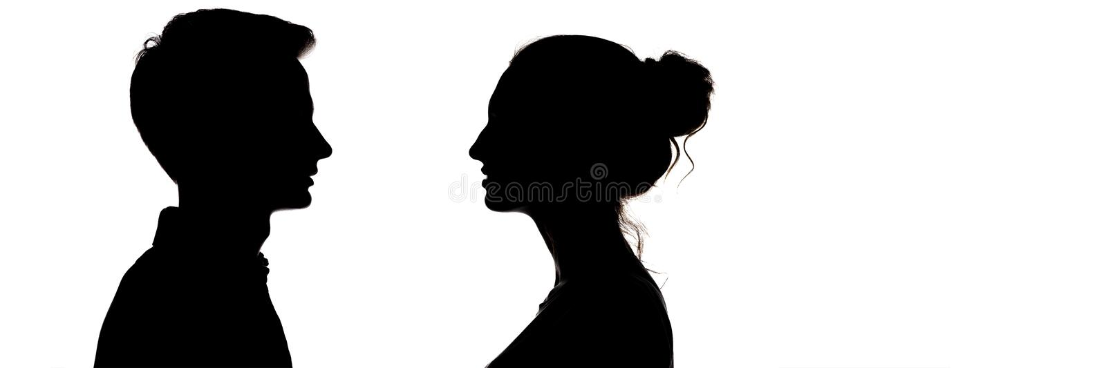 Silhouetteof a guy and a girl looking at each other, head profile of teenagers in love, the concept of relationships and feelings royalty free stock photo
