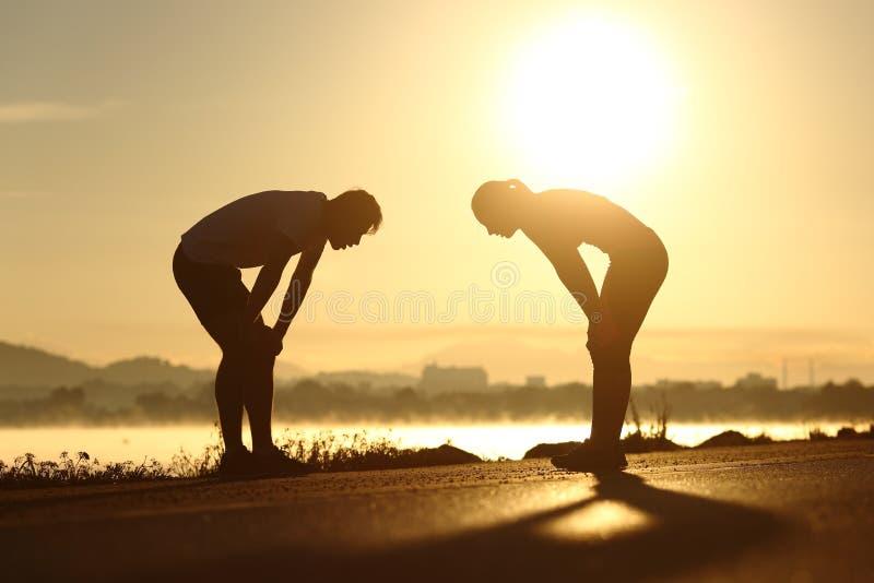Silhouettes épuisées et fatiguées de couples de forme physique au coucher du soleil photo stock
