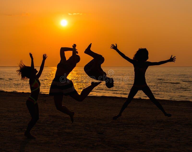 Silhouettes молодые люди имея потеху на пляже стоковые изображения rf