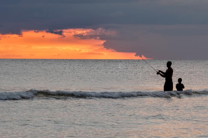 Silhouettes of of people fishing at sunset. Silhouettes of adult man and child fishing in light surf with orange sunset backdrop royalty free stock photography