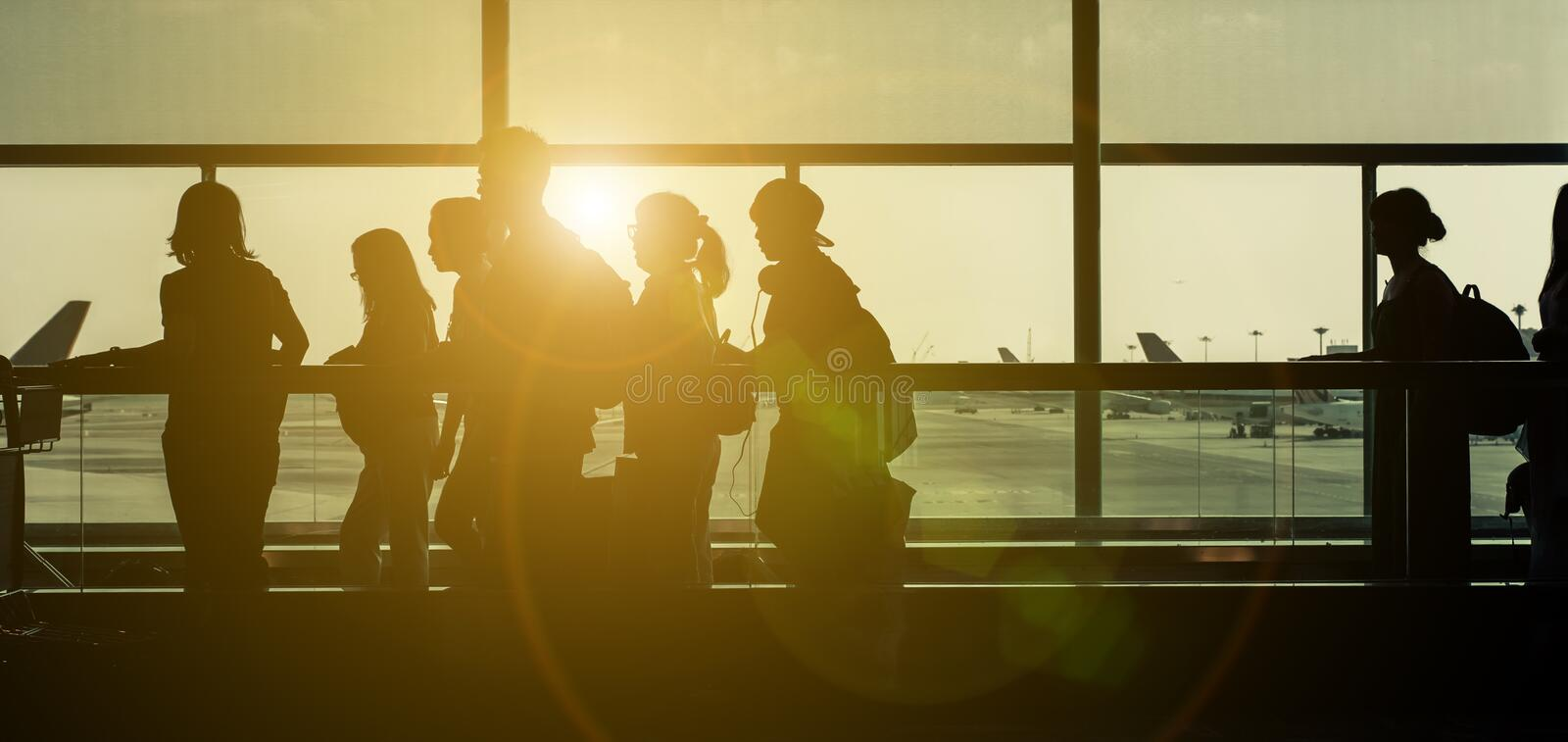 Silhouettes at the airport. Passengers on the sliding path with backlight royalty free stock photos