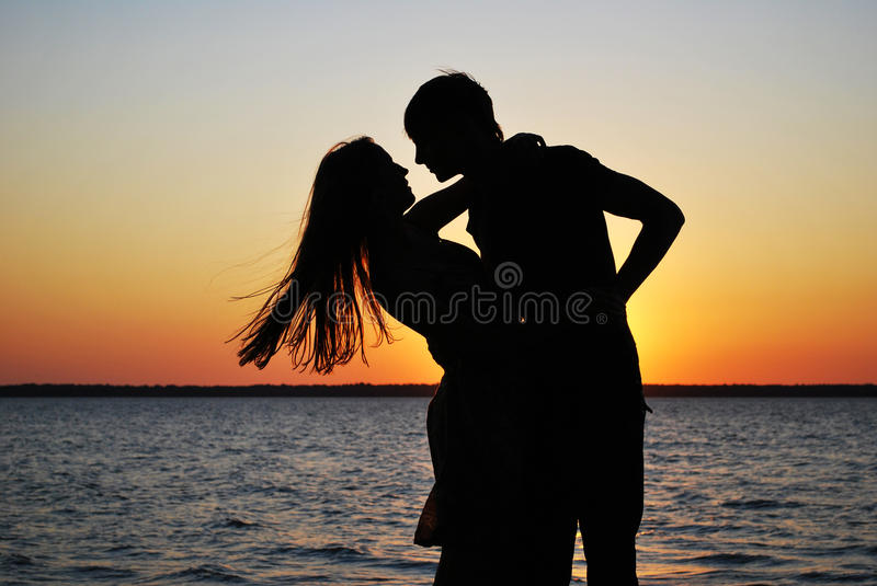 Silhouettes of amorous couple. On a background of a sunset royalty free stock photos