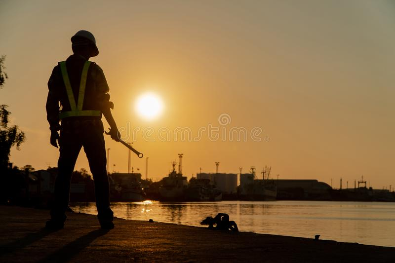 Silhouettes of asian man engineer holding wrenches and standing on shipyard and background is oil storage silo stock image