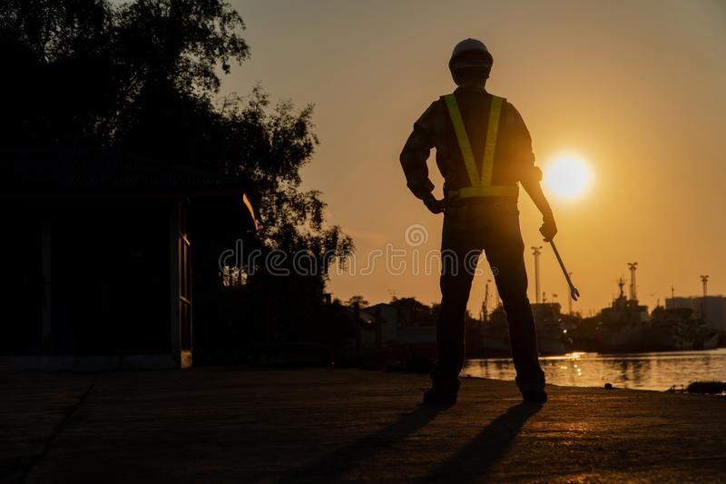 Silhouettes of asian man engineer holding wrenches and standing on shipyard and background is oil storage silo. stock photography