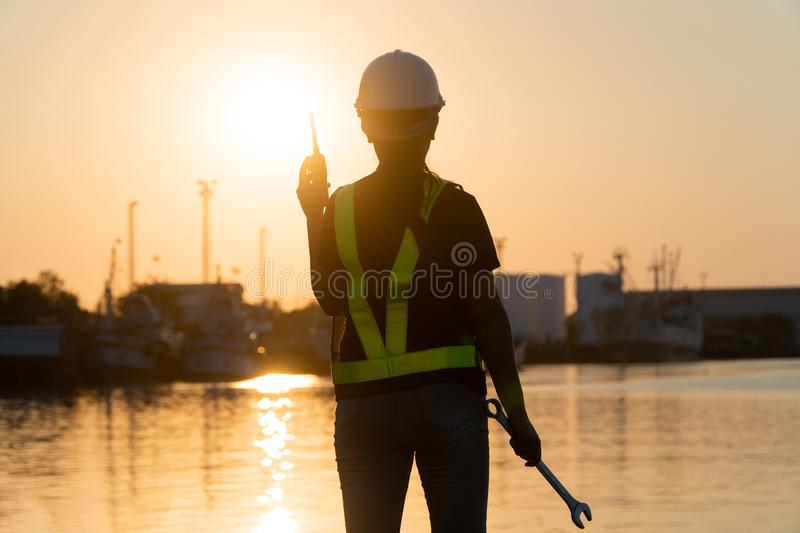 Silhouettes of asian woman engineer holding wrenches and radio communication walkie talkie she standing on shipyard. Background royalty free stock images