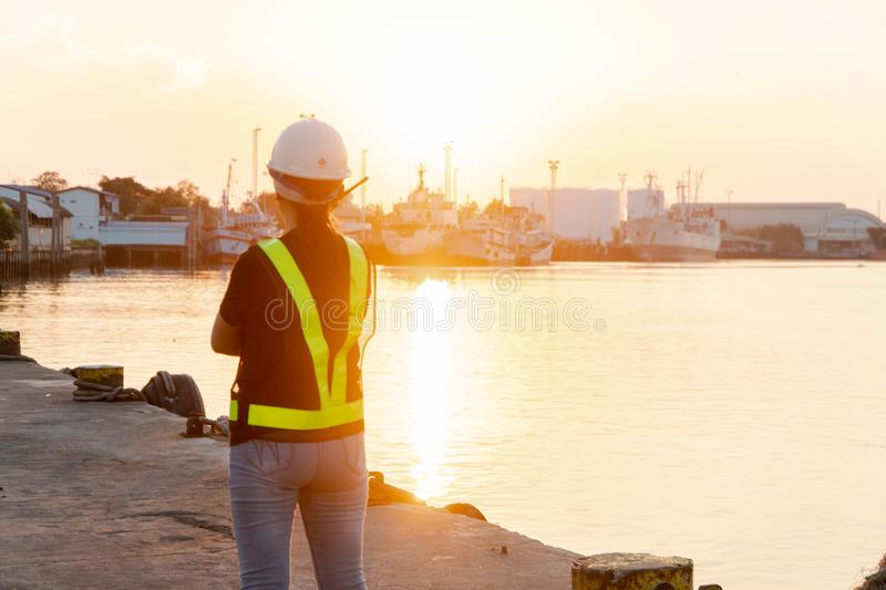 Silhouettes of asian woman engineer holding wrenches and radio communication walkie talkie she standing on shipyard. Background royalty free stock photos