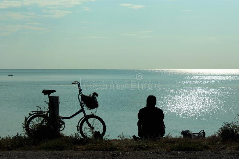 Silhouettes of bicycle and man sitting at the seashore and looking at sea.  royalty free stock photography