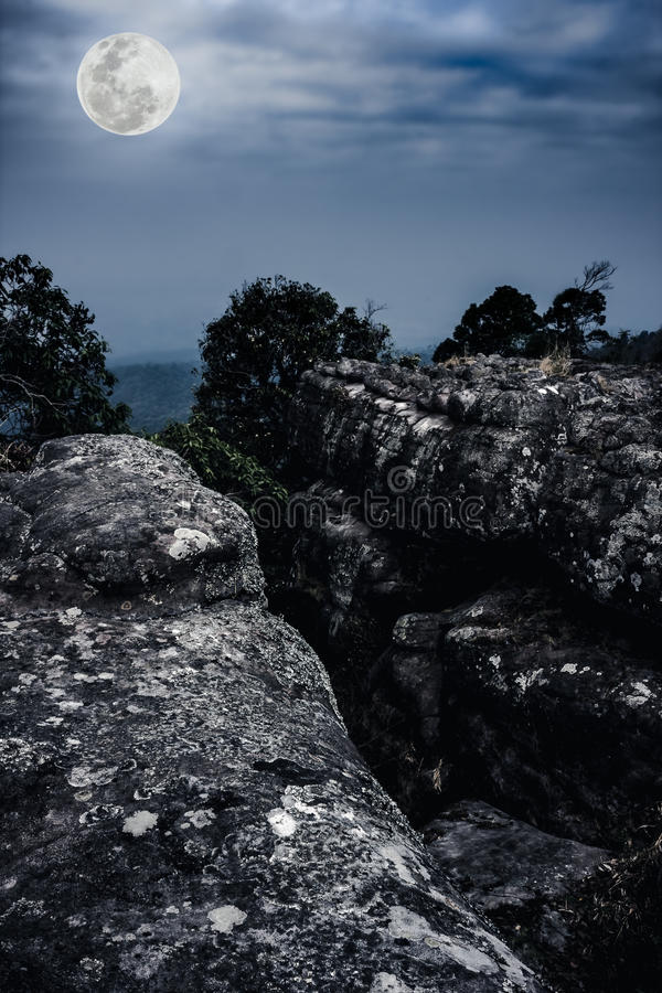 Silhouettes of boulders against blue sky and beautiful full moon royalty free stock image
