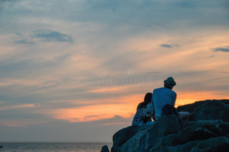 Silhouettes boy and girl at sunset over the tropical sea. Young man and girl sit on rock and look at seascape. Rear view. royalty free stock image