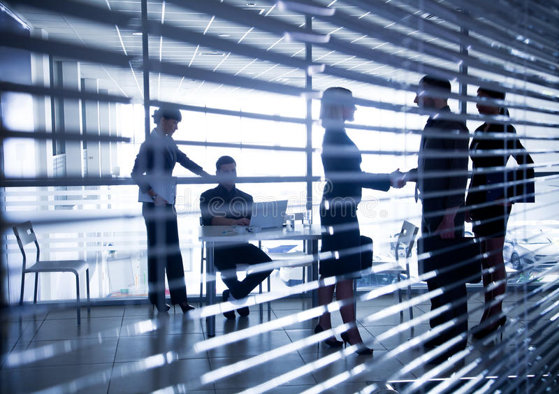 Silhouettes of business people through the blinds. Several silhouettes of businesspeople interacting background business centre stock images
