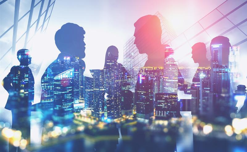 Silhouettes of business people in night city. Silhouettes of business people discussing work with double exposure of night cityscape over skyscraper background stock illustration