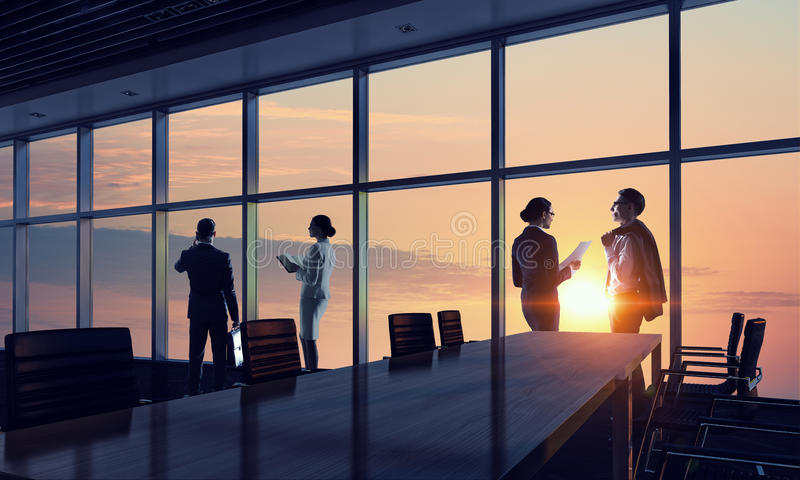 Silhouettes of Business People in Office. Mixed media . Mixed media royalty free stock image