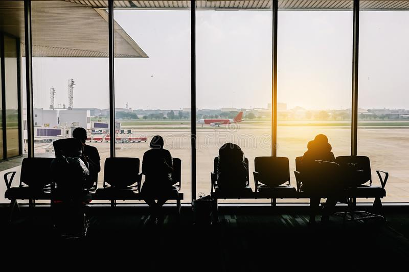 Silhouettes of business people traveling on airport; waiting at the plane boarding gates. In airport stock photography