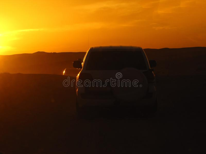 Silhouettes of cars in the desert in the rays of the setting sun stock photo