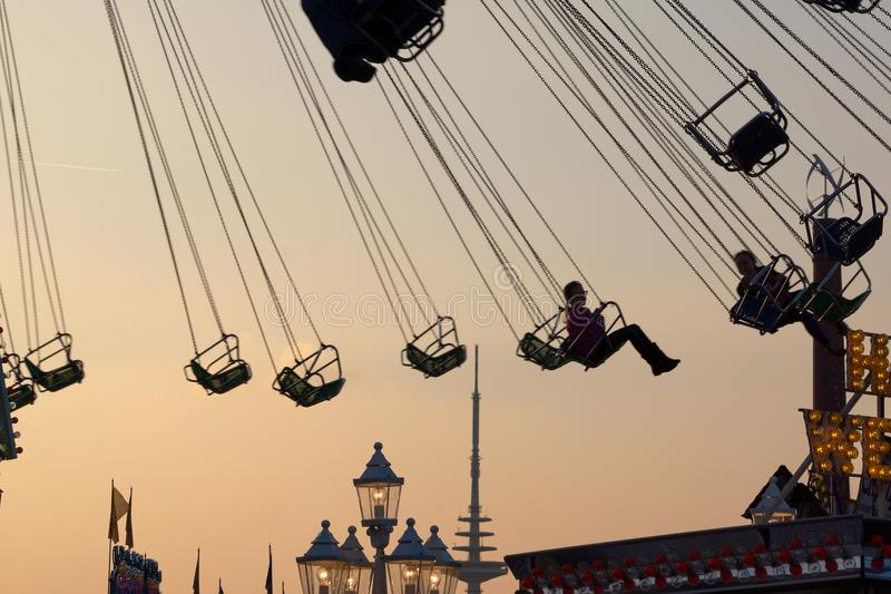 Silhouettes of chairoplane chains and chairs stock photo