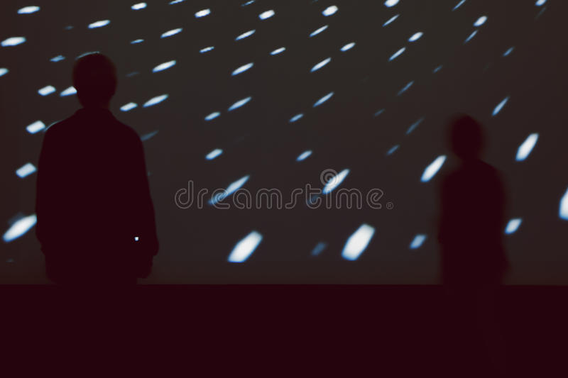 Silhouettes of children in front of large light screen. Silhouettes of two children standing in front of a large screen displaying a light show of patterns royalty free stock image