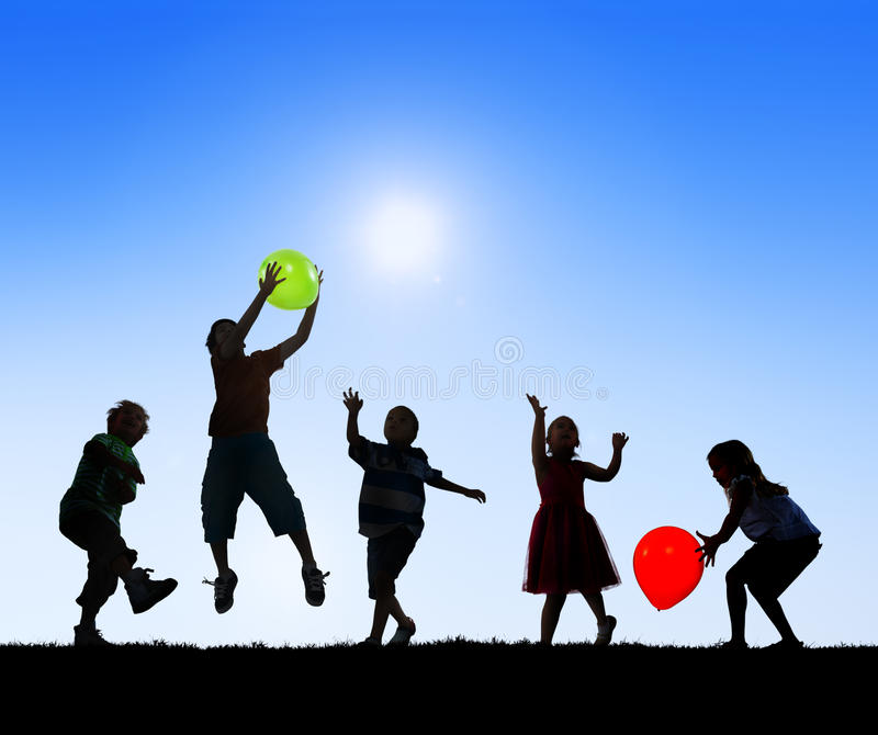 Silhouettes of Children Playing Balloons Outdoors royalty free stock photo