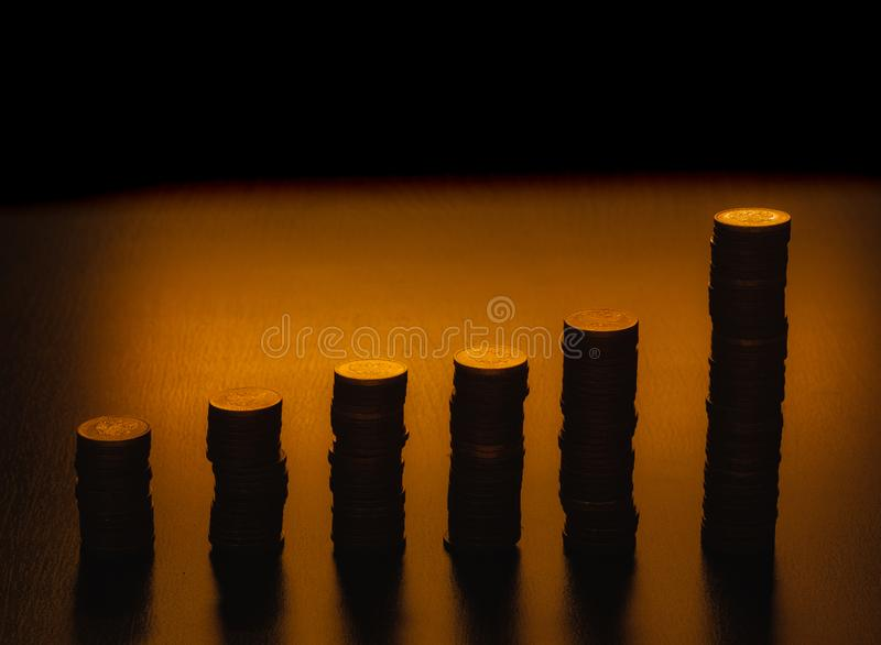 Silhouettes of coin stack. Stacks of coins of various heights. Vertical bar chart. royalty free stock images