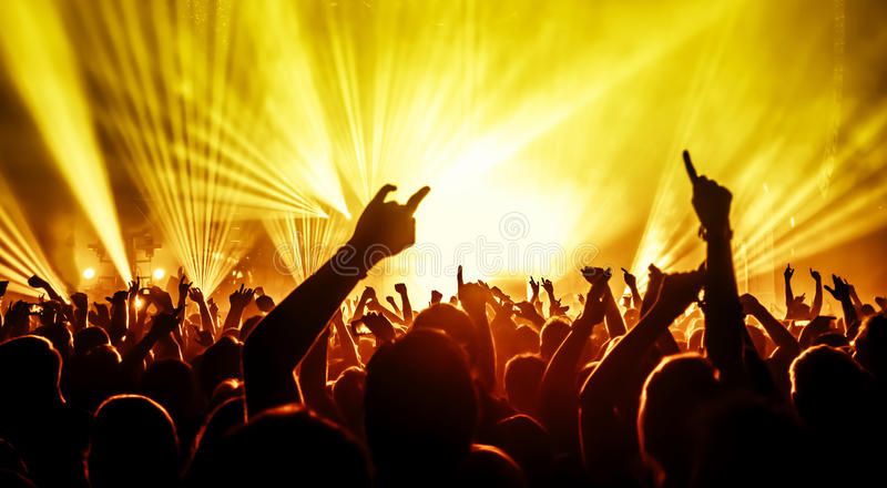 Silhouettes of concert crowd. In front of bright stage lights stock photos