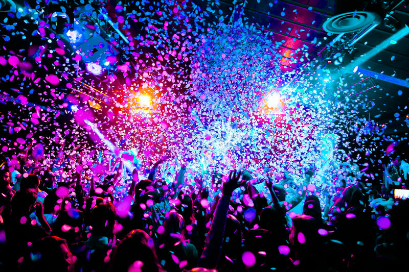 Silhouettes of concert crowd in front of bright stage lights with confetti. Silhouettes of concert crowd in front of bright stage lights with colourful stock image