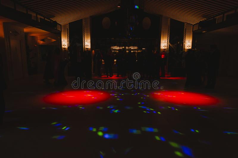 Silhouettes of concert crowd in front of bright stage lights. Disco and nightlife concept stock photos