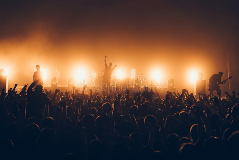 Silhouettes of concert crowd in front of bright stage lights. A sold out crowd on rock concert. Crowd of fans at music festive. Pa royalty free stock photos