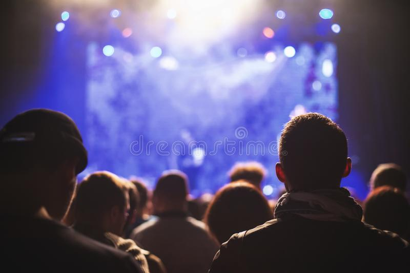 Silhouettes of a concert crowd in front of an illuminated stage in a nightclub. stock photo